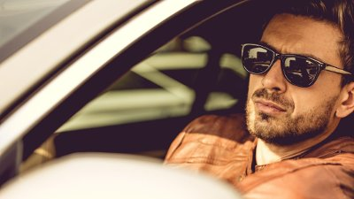 Living life on my own terms! Handsome european man driving his luxury car and looking at the camera.