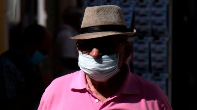 A man wearing a face mask walks along a street in Ronda on July 15, 2020. - More than 120 sources of contagion are currently active in Spain, which has led several regions, such as Catalonia, the Balearic Islands and Andalusia, to reinforce the mandatory use of face masks in streets or closed public spaces even if the social distance is kept.