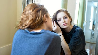 Woman Primping in Front of Mirror