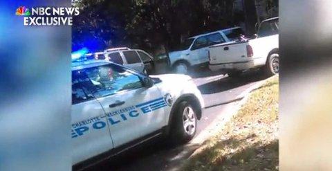 FRA VIDEOEN: Bildet er hentet fra videoen som du kan se lenger nede i artikkelen. Til venstre i bildet kan du se en politimann som sikter mot pick-upen til høyre i bildet der Keith Scott sitter.