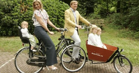 PÅ SYKKELTUR: Det nederlandske kronprinsparet Maxima og Willem-Alexander sammen med døtre Ariane (i setet) og Amalia og Alexia ved siden av hverandre.