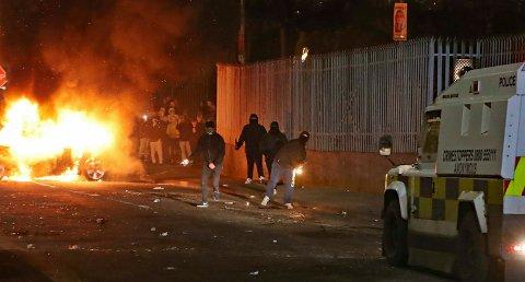 Maskerte menn går til angrep på politiet under opptøyene i Creggan i Derry. Foto: Niall Carson / AP / NTB scanpix
