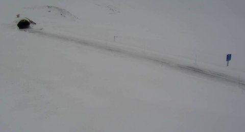 UVÆR: Det er uvær blant annet på Strynefjellet, og på fjellovergangen på riksvei 15 var det fredag morgen kolonnekjøring og lang ventetid. Bildet viser riksvei 15 ved Breidalen i retning mot Oppljostunnelen. Klokka 12 er det fortsatt kolonnekjøring.