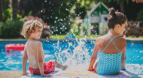 two kids having fun in pool two kids having fun splashing water in poolside