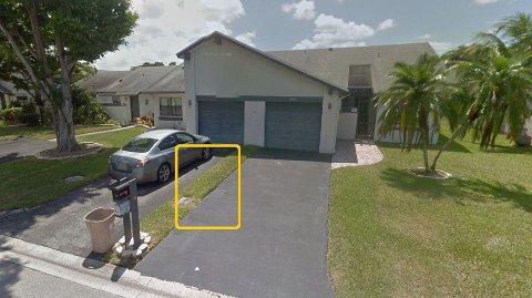 DYR FLEKK: Denne gressflekken på 30 meter kostet en mann over 80.000 kroner. Gresset er mellom to villa på Northwest 100th Way i Spring Lake i Florida, USA. Stripen med gress går ned til midten på garasjen, og gjennom bakgården.