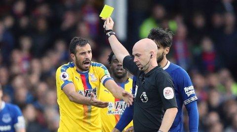 Crystal Palace-kaptein Luka Milivojevic (t.v.) får gult kort av dommer Anthony Taylor etter å ha felt Evertons Richarlison på Goodison Park.