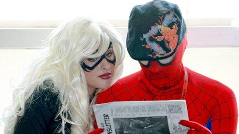 Angela Min og Shannon Seufert, kledt ut som Black Cat og Spiderman, leser konferansens program nøye.