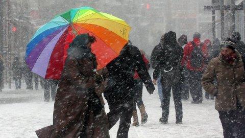 Dame med paraply går ute i snø og vind.