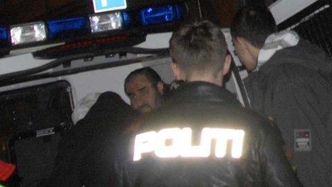 Mullah Krekar blir geleidet inn i en politibil.