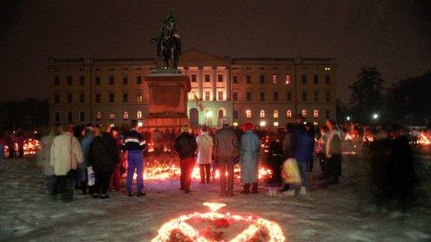 Folk tente lys og la fra seg blomster på Slottsplassen som en siste hilsen etter at kong Olav V døde i17. januar 1991.