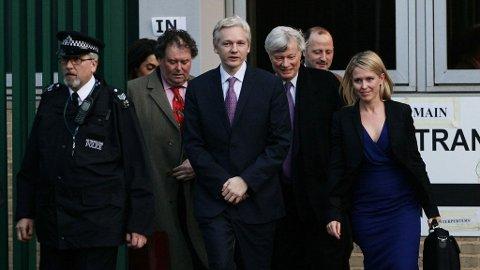 Julian Assange med sine advokater samlet rundt seg under dagens høring i London.