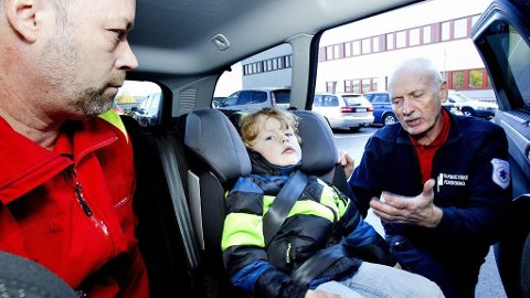 IKKE SLIK: Med den tykke jakka blir avstanden til beltet altfor stor, noe som øker sjansen for skader på barnet ved en kollisjon. Magebeltet sitter for høyt på magen, noe som kan føre til at barnet kan skli under beltet ved en bråstopp. Og beltet er dessuten for dårlig strammet til. Kim Ankersten (t.v.) og Trond Boye Hansen fant hele tre feil etter at jeg hadde sikret min sønn. Da hjelper det ikke stort at bilsetet er splitter nytt.