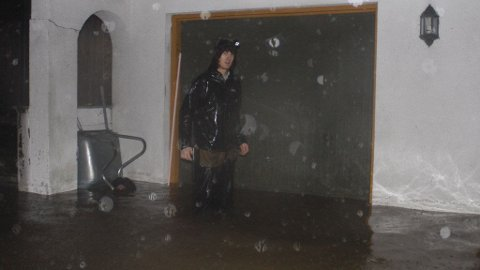 Huseier Vegar Aasen står med vann til over knærne utenfor sin garasje. Fra innsiden av garasjen er vannmassene like store og vannet trengte seg derfra videre inn i kjellerleiligheten.