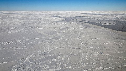 Scarred and chiseled sea ice in the Weddell Sea, where the DC-8 followed in CryoSat-2's tracks on Thursday's IceBridge flight. The DC-8's shadow appears as a dark speck in the lower right. Operation IceBridge is designed to record changes to Antarctica's ice sheets and give scientists insight into what is driving those changes.