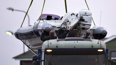 Nordmann skutt og drept under politiaksjon mot antatte smuglerei Ålbæk Havn. Smuglerbåden heises opp på lastebil for å bli kjørt bort mandag morgen.