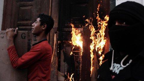 Supporterne til storklubben Al-Ahly er en politisk maktfaktor i Egypt. Her står egyptiske protestanter utenfor en brennende dør til en skole i Kairo i slutten av januar 2013. Opptøyene startet etter at det ble annonsert at 21 mennesker ble dømt til døden i forbindelse med en massakre hvor 70 Al-Ahly-supportere mistet livet.