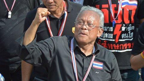 TRAPPER OPP AKSJONENE: Opposisjonslederen Suthep Thaugsuban hytter med neven utenfor lokalene til politiets spesialenhet DSI onsdag.