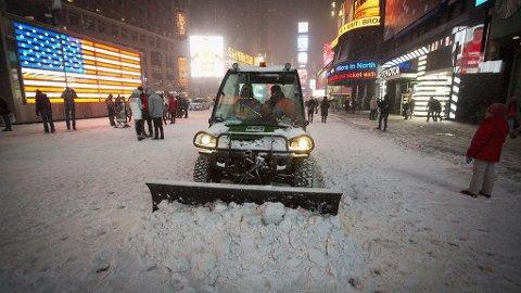 BRØYTER I NEW YORK: Snøplogen måtte fram på Times Square fredag etter snøfallet.