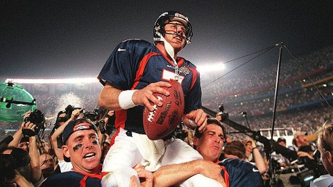 Denver Broncos quarterback John Elway (C) is carried by teammates Ed McCaffrey (L) and Bubby Brister (R) after the Broncos defeated the Green Bay Packers 31-24 to win Super Bowl XXXII in San Diego, CA 25 January. 1998-01-26