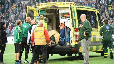 ALVORLIG: Erik Israelsson blir fraktet bort i ambulanse etter den voldsomme hodesmellen. FOTO: NTB scanpix