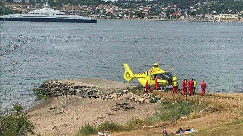 FRAKTET VEKK: Mannen som ble funnet livløs i vannet utenfor Festestranda blir nå fløyet vekk i luftambulansen.