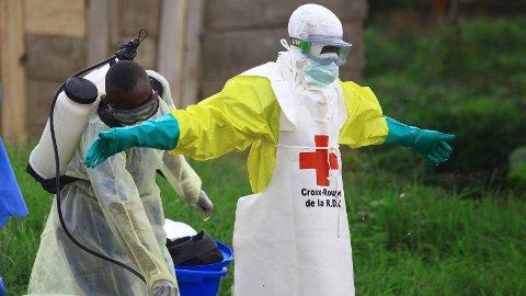 En helsearbeider sprayer desinfiseringsmiddel på en kollega på et behandlingssenter for Ebola i Beni øst i Kongo. Ebolautbruddet er nå det verste i landets historie. Foto: Al-hadji Kudra Maliro / AP Photo / NTB scanpix