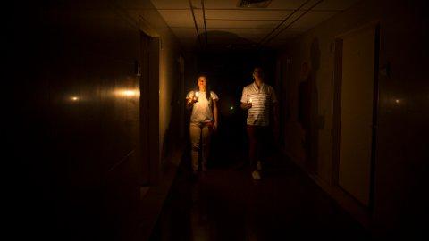 MØRKLAGT: Familien til en pasient går i gangene på et sykehus med stearinlys.