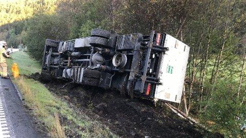 VELTET: Lastebilen veltet ned skrenten, og nå er det fare for diesellekkasje i elven til høyre i bildet.