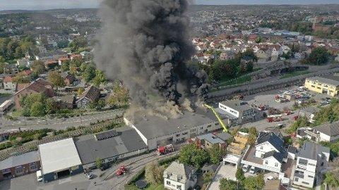 Ved 12-tiden tirsdag meldte politiet om brannen i et forretningsbygg i Fredrikstad sentrum. Dronebildet viser at det er kraftig brann i bygningen.