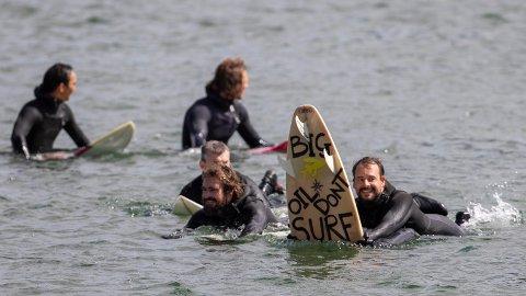 SURFEDEMO: En såkalt paddle-out går av stabelen søndag i havnebassenget utenfor Operaen. Her er surferne som demonstrerer mot Equinors planlagte oljeleting i Australbukta.