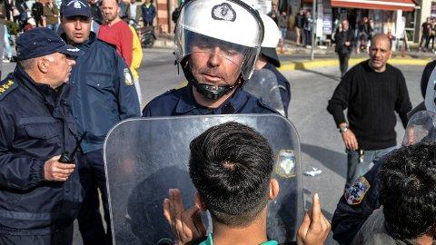 En migrant snakker med en gresk politimann under et mindre sammenstøt på Lesvos etter at lokalbefolkningen hadde stengt tilgangen til flyktningleiren Moria. Foto: AP / NTB scanpix