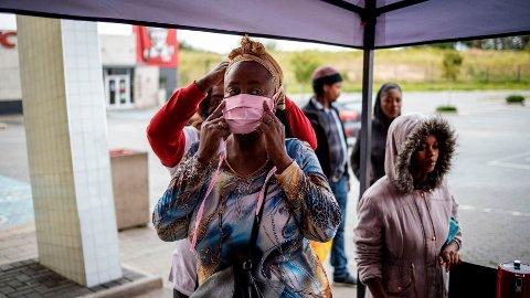 KORONA I AFRIKA: Her får en kunde i en butikk i Johannesburg, Sør-Afrika, hjelp til å sette på seg et munnbind.