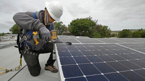 INSTALLERER: En amerikansk arbeider installerer solcellepaneler på et tak i California. I Norge ble om lag 60 prosent av all ny kapasitet installert på nærings- og industribygg i Norge.