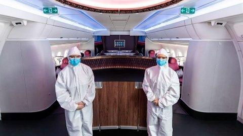 Kabinansatte fra Qatar Airways utstyrt med smitteverndrakt.