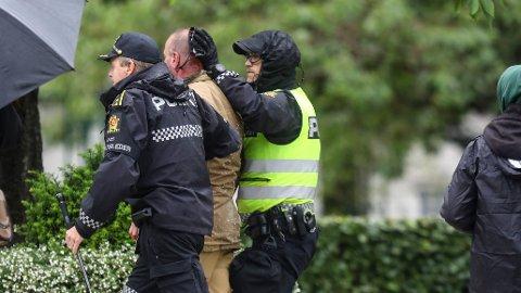 Sian-leder Lars Thorsen geleides bort fra podiet mens det ser ut som han blør fra hodet, etter at det brøt ut uroligheter under Sians markering på Festplassen i Bergen lørdag.