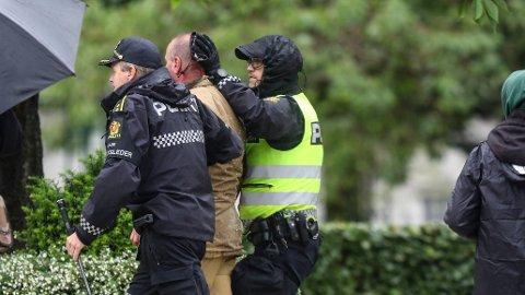 SKADET: Sian-leder Lars Thorsen geleides bort fra podiet etter at han ble slått under en markering i Bergen i august. Nå har politiet avsluttet oppfølgingen av ungdommene som ble innbrakt.