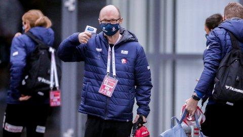 Håndballforbundets lege Nils Ivar Leraand på vei ut av bussen med febermåler i hånda.
