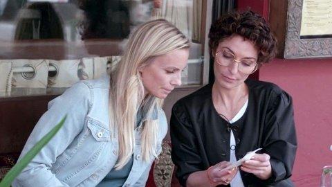 GÅR MYE PENGER: Lisa Tønne viser forbrukerøkonom Silje Sandmæl i DNB kvitteringen fra et restaurantbesøk, hvor hun hentet take away-mat. Det er én av postene Tønne bruker mye penger på.