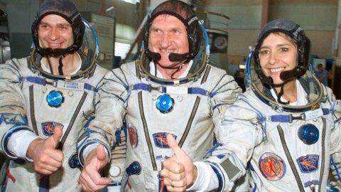 Den franske astronauten Claudie Haignere (til høyre) gir tommelen opp til kameraet sammen med sine russiske kosmonaut-kolleger. Foto: Mikhail Metzel / AP / NTB