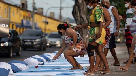 MINNER DE DØDE: Innbyggere i Rio de Janero legger roser på madrasser som symbol og minne om de som har dødd i forbindelse med covid-19. Bildet er tatt i forbindelse med en protest mot hvordan brasilianske myndigheter har håndtert pandemien, organisert av the Rio de Paz NGO, fremfor sykehuset Ronaldo Gazolla.