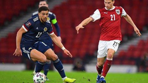 Che Adams (t.v.) kan starte sin første søndagens kamp for Skottland søndag. Her er Southampton-stjernen i duell med den østerrikske forsvarsspilleren Stefan Lainer.