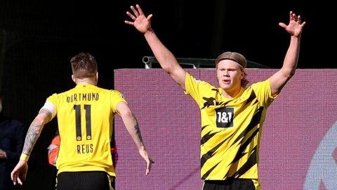 Erling Braut Haaland jubler sammen med lagkamerat Marco Reus etter å ha scoret to mål mot Wolfsburg.