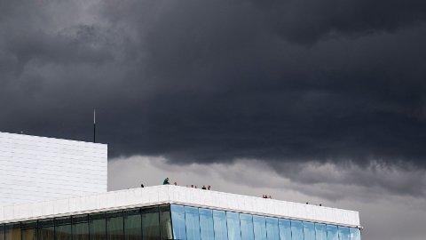 Mørke skyer med kraftig regnvær smyger seg inn over Operaen i Oslo.