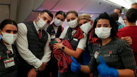 Kabinpersonalet på et Turkish Airlines-fly poserer med datteren til Soman Noori som ble født på flyet med kabinpersonalets hjelp. Foto: Turkish Airlines via AP / NTB