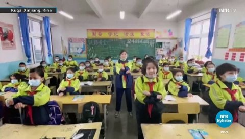 En skoleklasse med glade uigur-barn feirer tilsynelatende at de snart skal begynne på ungdomsskolen.