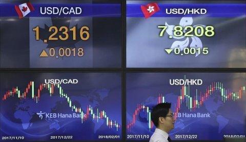 Fremgang for flere asiatiske nøkkelbørser tirsdag 13.02.18. Illustrasjonsfoto: En valutamegler på børsen i Seoul foran infoskjermer 01.01.18.