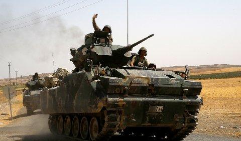 Tyrkiske fly har bombet områder nord i Syria og drept 20 IS-medlemmer, ifølge tyrkiske militærkilder. Her vinker en tyrkisk soldat fra toppen av en stridsvogn like ved den tyrkisk-syriske grensen.