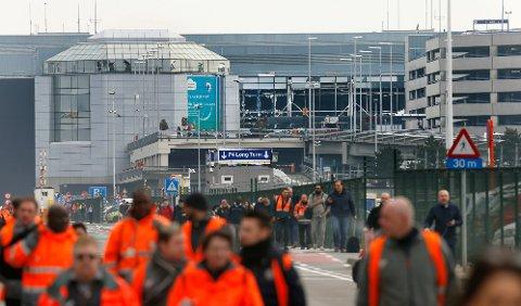 Folk evakuerer Zaventem lufthavn nær Brussel etter eksplosjonene tirsdag.