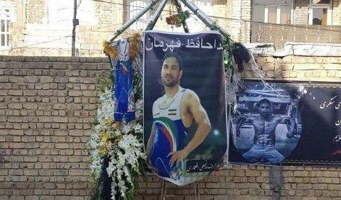 Iranere har hengt opp blomster og en banner til minne om Navid Afkari i hjembyen Shiraz.