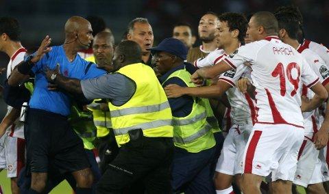 AMPERT: Dommer Rajindraparsad Seechurn (til venstre) måtte ha hjelp fra vakter for å komem seg unna rasende tunisiske spillere etter Tunisias tap i kvartfinalen mot Ekvatorial-Guinea.